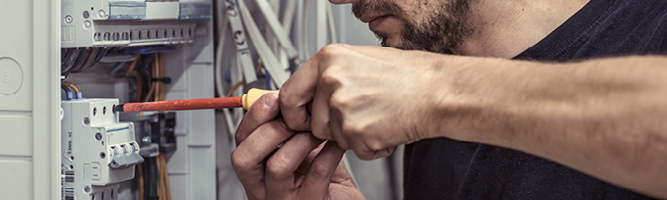 Worker using a screwdriver on converged technologies