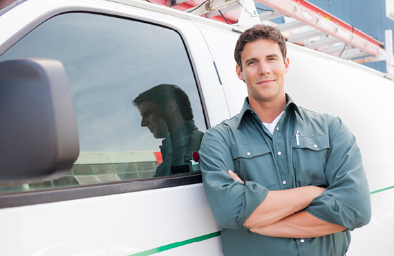 Man working and leaning up against a white van
